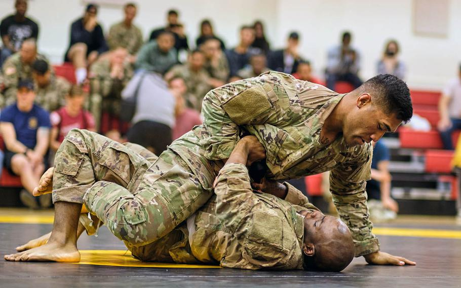 Pfc. Frazer Taua, top, and Sgt. Daquon Jeffress of 2nd Infantry Division compete during the Friday Night Fights debut tournament at Camp Humphreys, South Korea, on May 10, 2019.
