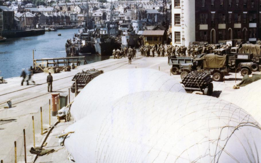American troops load onto infantry landing ships at a port in Weymouth, England in June 1944, where barrage balloons have been anchored for protection against strafing and low level bombings.