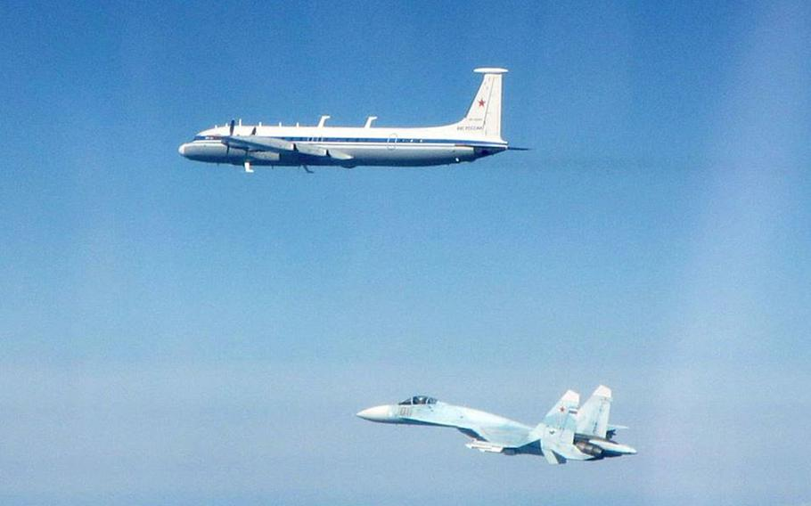 A Russian SU-27 Flanker fighter and an IL-22 aircraft fly along the Baltic coast, Thursday, May 16, 2019.