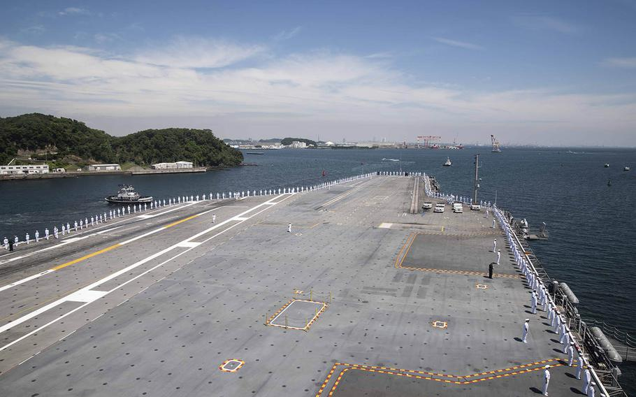 Sailors man the rails on the flight deck of the USS Ronald Reagan as the aircraft carrier departs Yokosuka Naval Base, Japan, Wednesday, May 22, 2019.