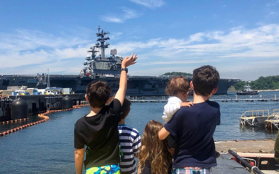 The children of Lt. Cmdr. Daniel Supple – James, 9; Charles, 7; Juliet, 4; Alexander, 1; and William, 12 – watch as the USS Ronald Reagan departs Yokosuka Naval Base, Japan, Wednesday, May 22, 2019.