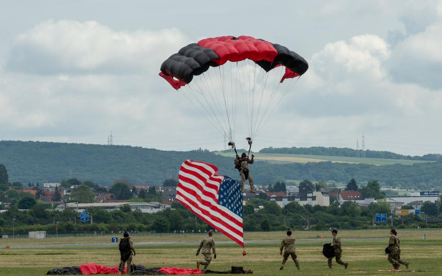 A parachutist lands with the American flag in tow during the 70th anniversary commemoration of the end of the Berlin Airlift at Clay Kaserne airfield, Monday, June 10, 2019.