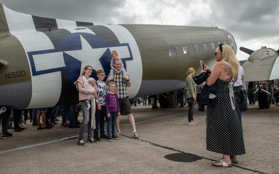 A family poses for a portrait in front of a C-47 Skytrain during the 70th anniversary commemoration of the end of the Berlin Airlift at Clay Kaserne airfield, Monday, June 10, 2019.
