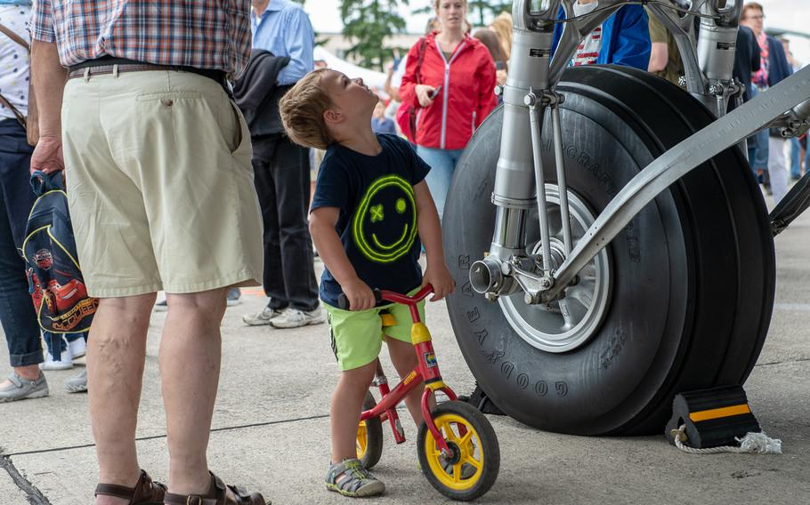 A young cyclist looks up at a C-47 Skytrain during the 70th anniversary commemoration of the end of the Berlin Airlift at Clay Kaserne airfield, Monday, June 10, 2019.   s