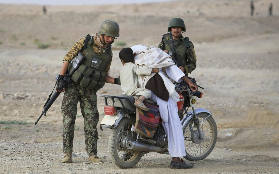 An Afghan soldier helps a child off a motorcycle while conducting searches at a vehicle checkpoint in Shekasteh Tappeh, Helmand province, Afghanistan, July 2014. Afghanistan surpassed Syria as the world's least peaceful country, according to a report from an Australia-based think tank.