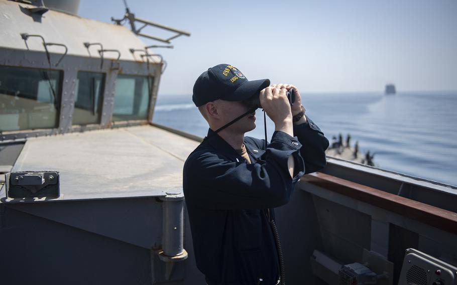 Lt. j.g. Christopher Monroe looks through binoculars on the bridge of the guided-missile destroyer USS McFaul while transiting the Strait of Hormuz, May 3, 2019. Iranian lawmakers have pushed a bill in the nation?s parliament that would impose tolls on foreign or ''unfriendly'' vessels transiting the busy strait.