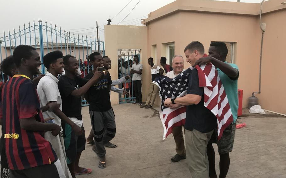 Djiboutian Doudou Roblah drapes a flag over U.S. Army Capt. Noah Hodges' shoulders as Capt. Mike Volk and Roblah's friends look on outside a vocational school in the capital of Djibouti on Thursday, June 13, 2019. U.S. Embassy officials say an English language discussion group the soldiers lead at the school helps to support diplomatic and development efforts in Africa.