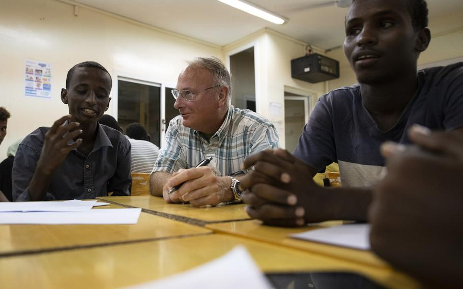 U.S. Army Capt. Michael Volk, a civil affairs officer, works with students during the first-ever English language discussion group in the neighborhood of Balbala, in the capital of Djibouti, Nov. 29, 2018.