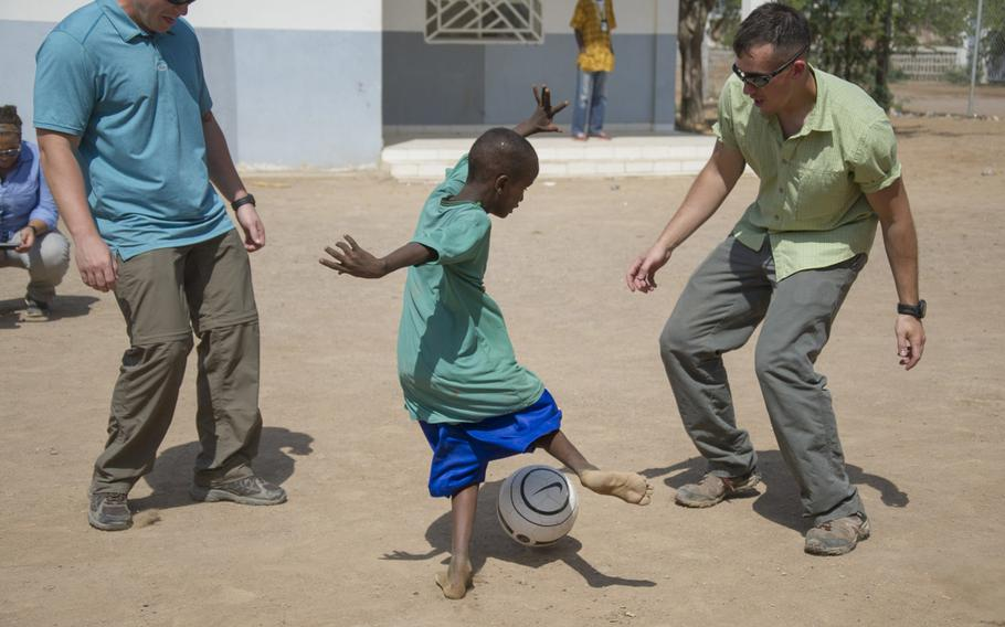 U.S. Army Civil Affairs personnel play soccer with a boy in Djibouti in 2016.