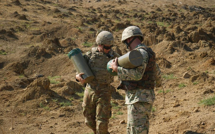 A Georgian and a U.S. soldier, assigned to the Regimental Engineer Squadron, 2nd Cavalry Regiment, carry casings for C-4 explosives during Agile Spirit 19 near Tbilisi, Georgia, July 30, 2019.