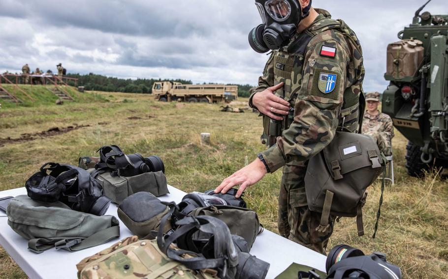 A Polish soldier identifies gear from various NATO allies while wearing a gas mask during the Interoperability Games in Bemowo Piskie, Poland, Saturday, August 3, 2019.