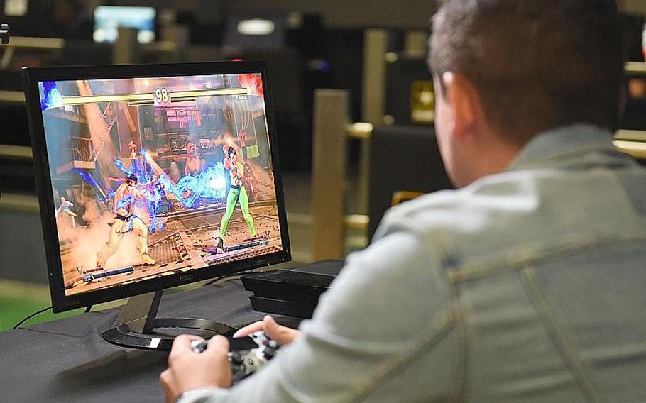 """Gamer Ziggy113, a U.S. Army soldier, launches a """"Hadouken"""" fireball as Ryu, in the Street Fighter V tournament at Vilseck, Germany, Saturday, Aug. 17, 2019."""