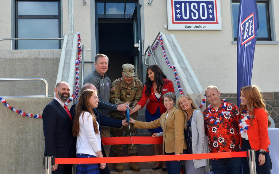 Konrad Braun, area director, USO Kaiserslautern, Col. Jason Edwards, U.S. Army Garrison Rheinland-Pfalz commander and Megan Rivera, manager of the Baumholder USO, top row, left to right, and other dignitaries, cut the ribbon at the grand opening of the new USO center on Smith Barracks in Baumholder, Germany, Sept. 9, 2019.