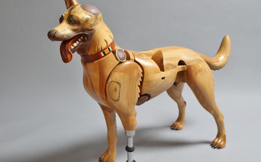 Laminated and carved sycamore and cherry, copper, nickel plate, and oil paint. This Belgian Malinois with the Navy Seal trident is a reminder of our wounded veterans who returned home from Iraq, many with injuries. The all-too-common injuries represented here include a traumatic brain injury and the loss of a limb and an eye from an improvised explosive device.