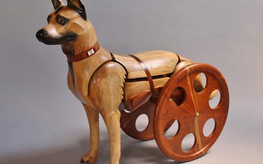 Laminated and carved sycamore and cherry, copper, and oil paint. This Malinois wears the service ribbon from Afghanistan and is a double amputee aided by a sling wheelchair. The wheels are free-turning, more like those designed for wheelchairs for humans. Note the Purple Heart.