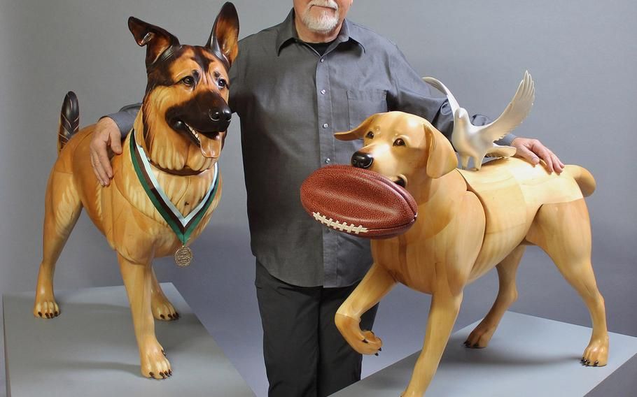 Artist Jim Mellick with his wooden sculptures of  Wounded Warrior Dogs Lucca K458 and Cooper K154. Their real-life counterparts were Marine Corps service dogs trained to detect explosives on assignment together during operations in Iraq.  Jim Mellick