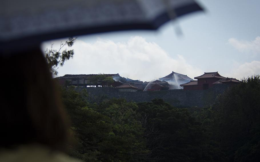 People watch as firefighters work to extinguish a blaze at Shuri Castle in Naha, Okinawa, Thursday, Oct. 31, 2019.