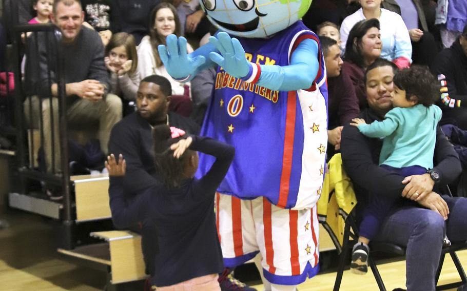 Harlem Globetrotters mascot Globie interacts with a fan during a game at the Dragon Fitness Center, Aviano Air Base, Italy, Nov. 12, 2019.