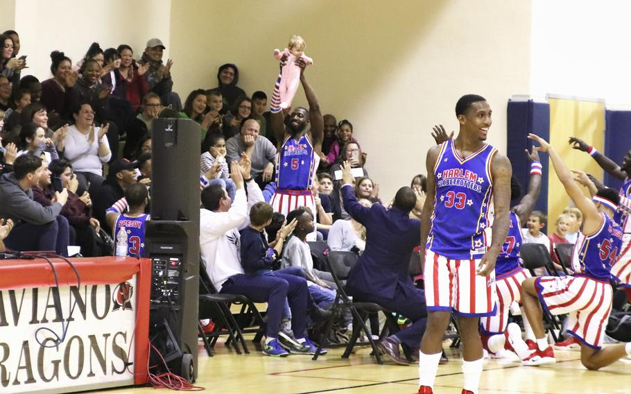 """Harlem Globetrotter Bulldog Mack lifts a baby in the crowd as the """"Lion King"""" theme song plays during a game at the Dragon Fitness Center, Aviano Air Base, Italy, Nov. 12, 2019."""