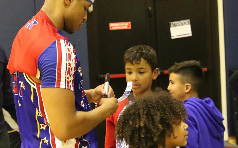 Harlem Globetrotter Jet Rivers signs autographs for fans after a game at the Dragon Fitness Center, Aviano Air Base, Italy, Nov. 12, 2019.