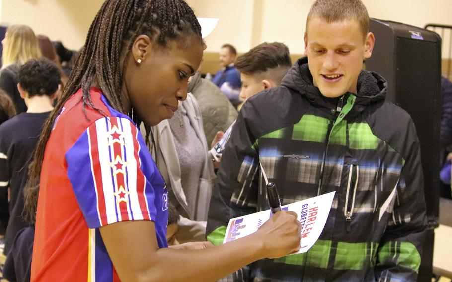 Harlem Globetrotter TNT Lister signs autographs for fans following a game at the Dragon Fitness Center, Aviano Air Base, Italy, Nov. 12, 2019.
