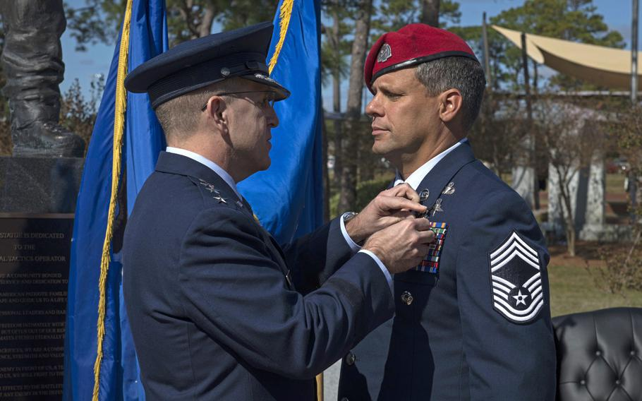 Lt. Gen. Jim Slife, commander of Air Force Special Operations Command, pins the Silver Star medal onto Chief Master Sgt. Chris Grove during a ceremony at Hurlburt Field, Fla., Nov. 15, 2019.