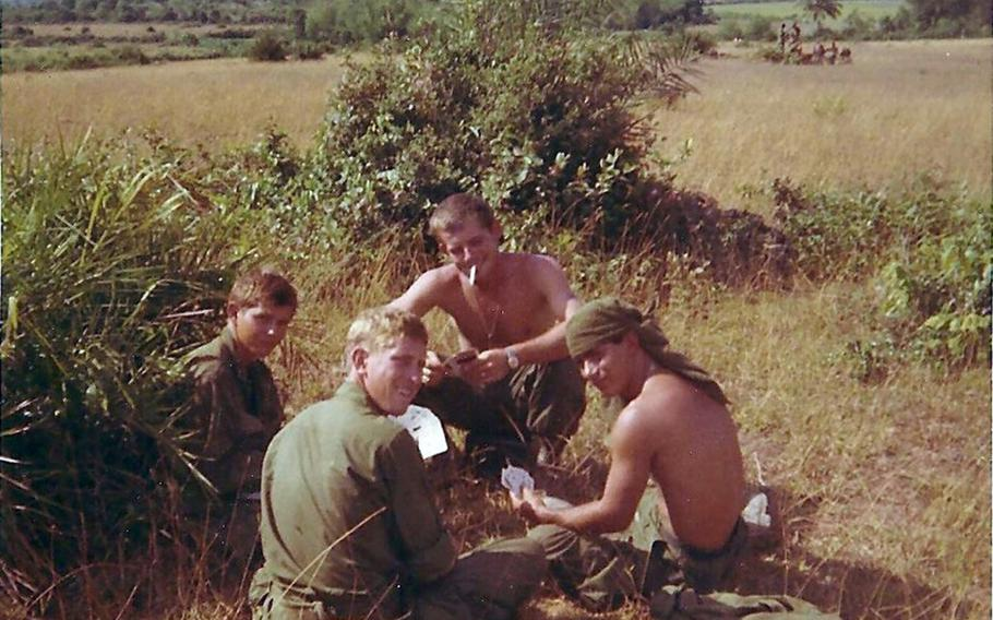 Spc. Clifford Van Artsdalen, left, plays cards with his fellow platoon members on May 5, 1968, as they await a helicopter shuttle to Hill 352 on Nui Hoac Ridge, South Vietnam.