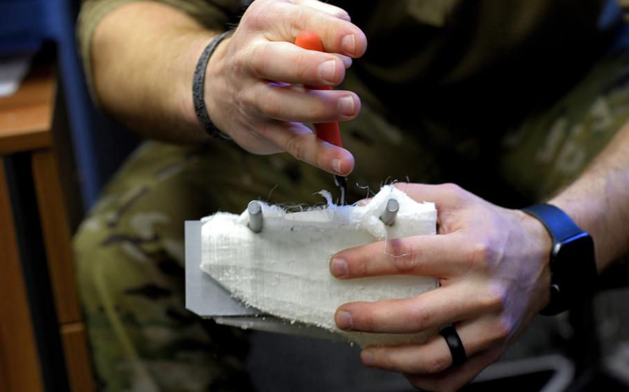 Staff Sgt. William Riddle, a 48th Civil Engineer Squadron Explosive Ordnance Disposal NCO, carves dry molding off of a recently printed training aid at Royal Air Force Lakenheath, England, Nov. 19, 2019.