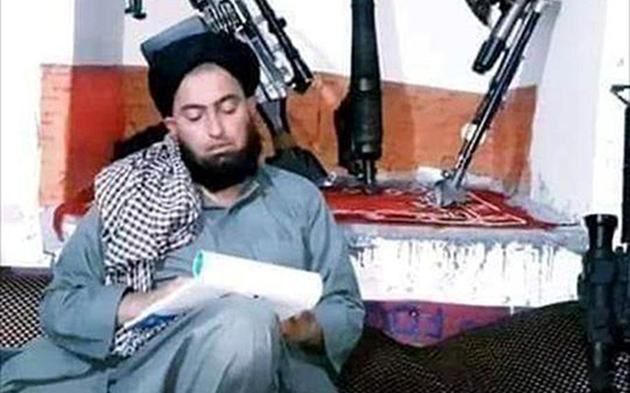 Mullah Nangyalai, a regional leader of the Taliban breakaway faction led by Mullah Mohammad Rasoul, writes on a notepad in an undated photo provided by friends of his. Nangyalai was killed in an airstrike on Jan. 8, 2020 in western Afghanistan, the Rasoul splinter group said.
