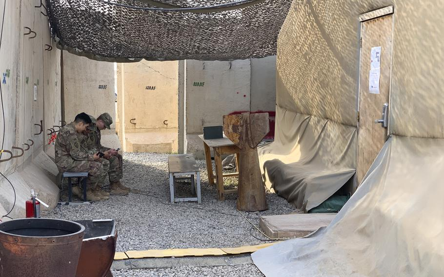 U.S. soldiers view their smartphones in a break area outside a command center on Qayara Airfield West in Iraq on Thursday, Dec. 26, 2019.