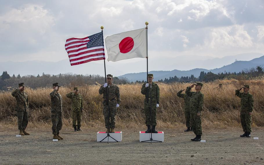 Members of the 31st Marine Expeditionary Unit and the Japan Ground Self-Defense Force's 12th Infantry Regiment salute their flags during the opening ceremony for exercise Forest Light at Camp Oyanohara in Kyushu, Japan, Jan. 18, 2020.