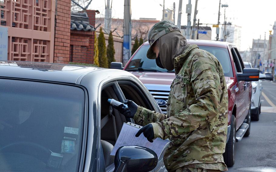 Pvt. Hector Mercado, 23, of the 25th Transportation Battalion, checks temperatures before allowing people to enter Camp Walker in the coronavirus-hit city of Daegu, South Korea, Saturday, Feb. 22, 2020.