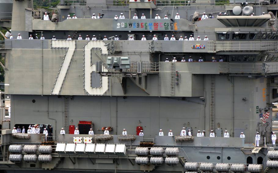 Sailors man the rails of the aircraft carrier USS Ronald Reagan as it departs Yokosuka Naval Base, Japan, in May 2018.