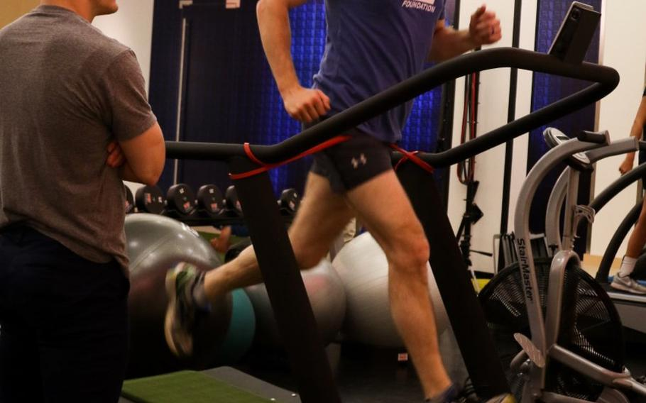 Former Green Beret Kevin Flike runs on a treadmill with his fitness coach, Jordan Lowry, while training for the Boston Marathon at the TB12 Sport Therapy Center, Foxborough, Mass., in April 2018. Flike, 35, promised himself he would run a marathon after getting shot by a Taliban sniper in Afghanistan in 2011.