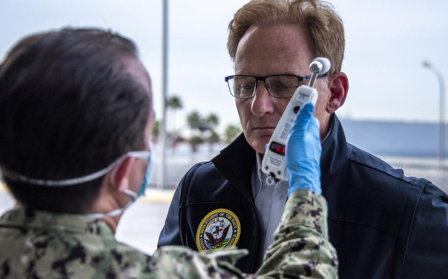 Acting Secretary of the Navy Thomas B. Modly has his temperature read as part of a coronavirus screening in Los Angeles, March 31, 2020. Modly criticized the former captain of the aircraft carrier USS Theodore Roosevelt, Capt. Brett Crozier, over the ship's loudspeakers in a speech to the crew Monday. Modly fired Crozier last week after a memo asking for the evacuation of sailors from the ship was leaked to the San Francisco Chronicle.