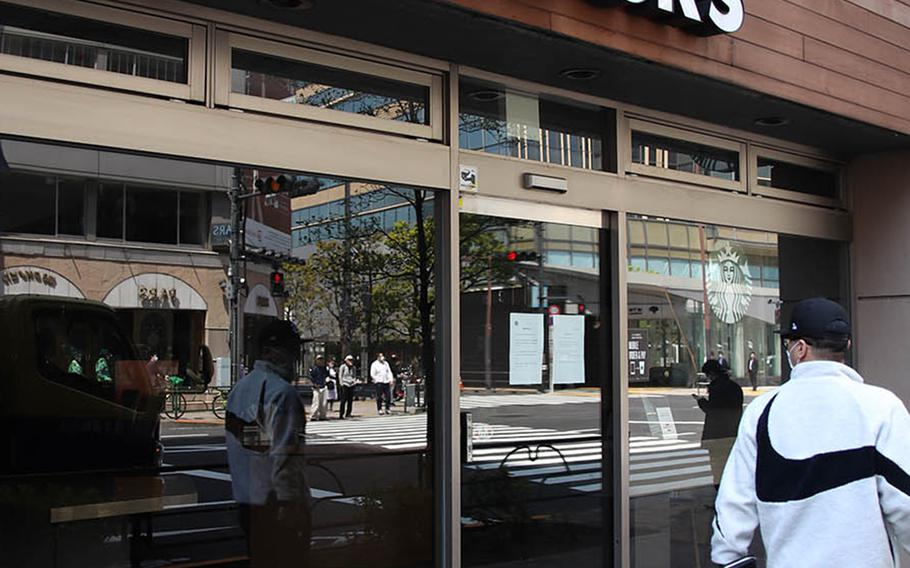 A man glances at a Starbucks in central Tokyo that's been shuttered because of the coronavirus, April 9, 2020.