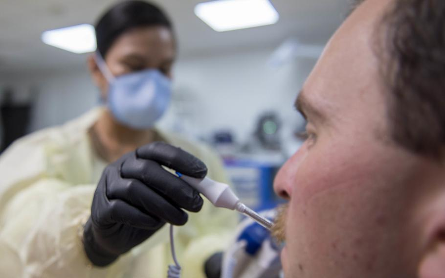 Navy Lt. Gail Evangelista, a nurse assigned to Naval Hospital Rota, Spain, takes a patient's temperature at the Michaud Expeditionary Medical Facility at Camp Lemonnier, Djibouti, April 16, 2020.