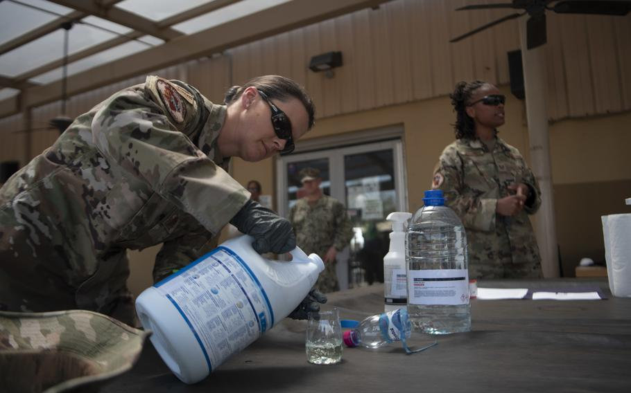 Air Force Maj. Leah Chapman, left, Combined Joint Task Force-Horn of Africa Surgeon Cell public health officer, demonstrates creating a cleaning solution using bleach and water during a training session for the high-traffic area disinfectant team at Camp Lemonnier, Djibouti, March 27, 2020.