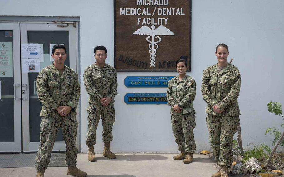 From left, Petty Officer 2nd Class Jerry Marquez and Petty Officer 2nd Class Wickbol Monno, Lt. Gail Evangelista and Cmdr. Hillary Meyer, assigned to Naval Hospital Rota, Spain, stand in front of Michaud Expeditionary Medical Facility at Camp Lemonnier, Djibouti, April 16, 2020. The four-member team augments critical positions at the camp during the coronavirus pandemic, enabling existing medical staff to treat trauma patients.