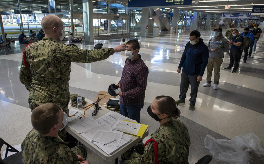 Staff assigned to Recruit Training Command process recruits as part of a preliminary health screening at Chicago O'Hare Airport in Chicago, Ill., April 21, 2020.