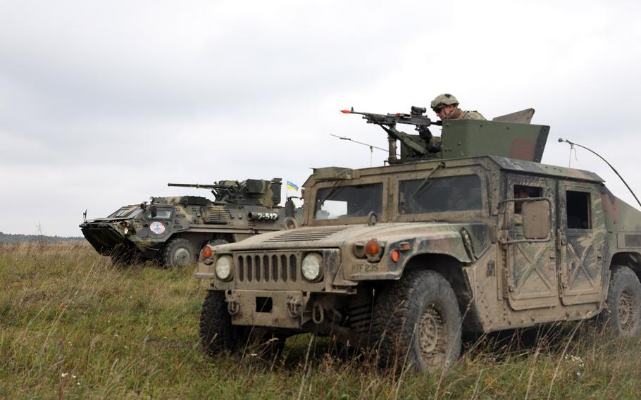 A firing squad from the 101st Airborne Infantry Division, in a Humvee, right, and a Ukrainian armored military vehicle from the 10th Mountain Assault Brigade prepare to engage targets during Rapid Trident 2019 in Yavoriv, Ukraine, Sept. 26, 2019. The Pentagon has earmarked $250 million to aid Ukraine, whose forces are battling Russian-backed separatists.  Kyle Larsen/U.S. Army