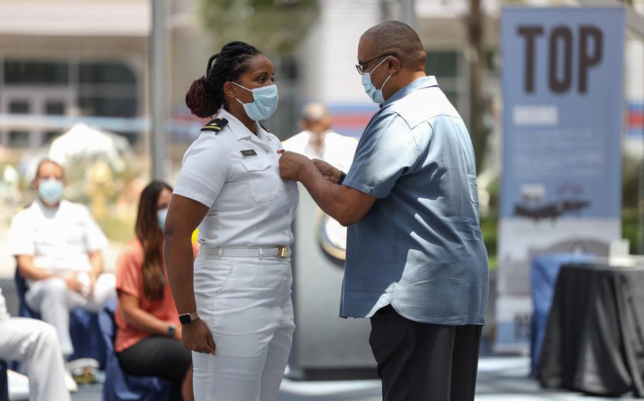 Ensign Breanna Thomas, left, a student at Naval Aviation Schools Command, receives the Purple Heart and the Navy and Marine Corps Commendation Medal during an awards ceremony held at the National Naval Aviation Museum, June 19, 2020. The ceremony recognized the bravery and selflessness of those service members and federal workers involved in the Dec. 6, 2019 shooting at Naval Air Station Pensacola, Fla.