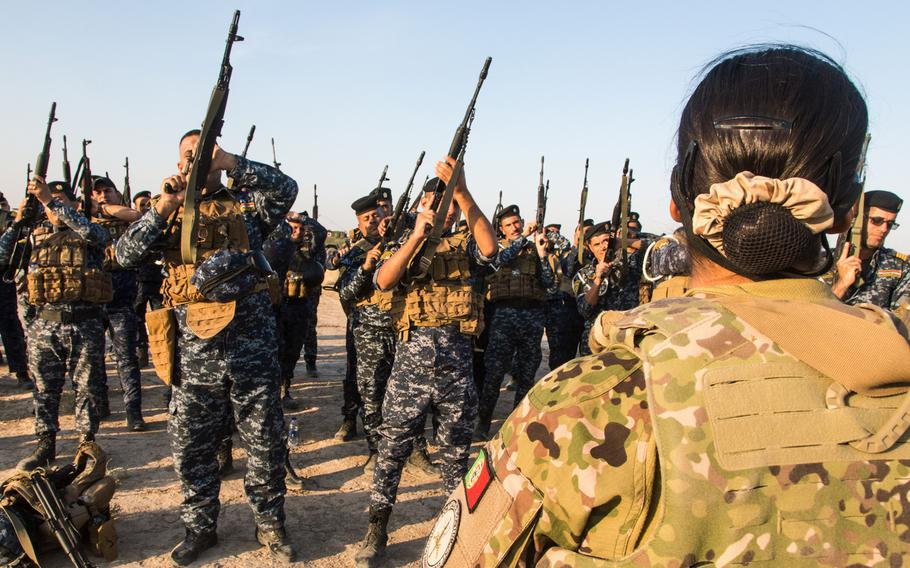 A Portuguese soldier teaches Iraqi Federal Police weapon safety with the AK-74 rifle at the Besmaya Range Complex in Iraq on Aug. 7, 2019. The U.S.-led coalition fighting the Islamic State is handing over the range and about $5 million in equipment to the Iraqi military as international forces draw down their presence in the country.