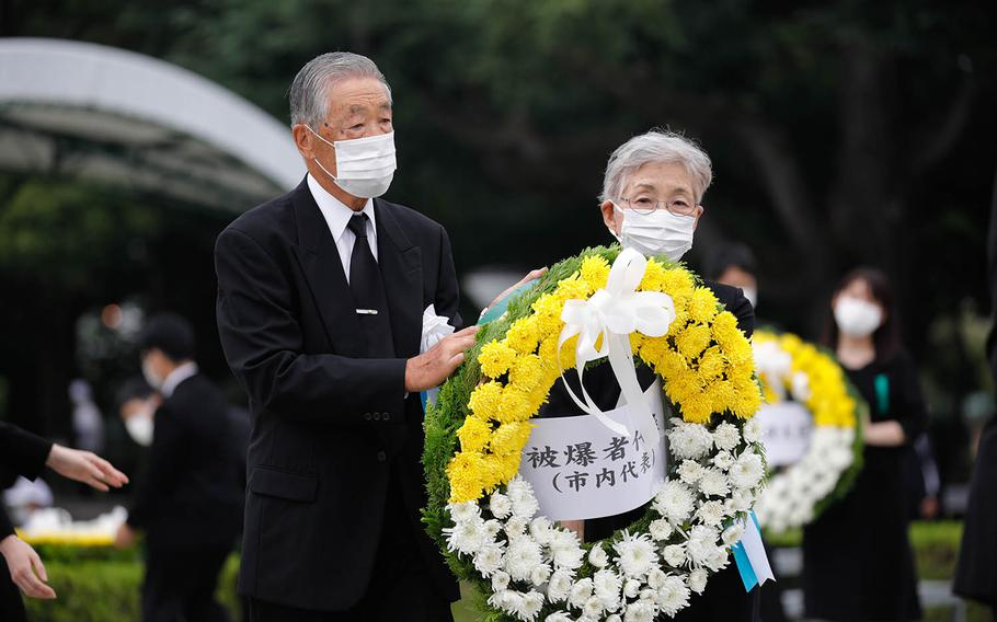 People lay a wreath at the cenotaph for the victims of the 1945 atomic bombing at Peace Memorial Park in Hiroshima, Japan, Aug. 6, 2020.