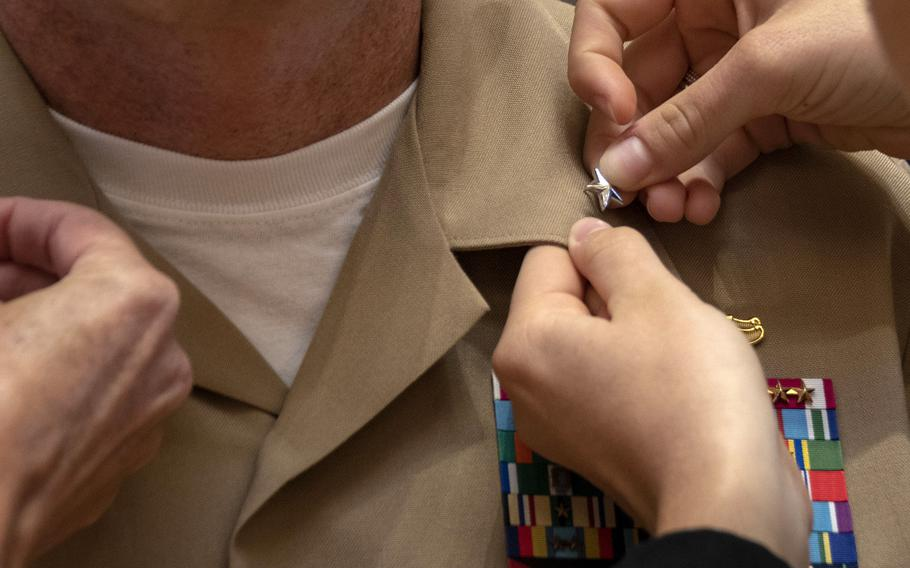 A rear admiral gets his star pinned to his uniform in 2019.  A recent Rand Corp. study said the armed services trains and promotes its flag officers in different ways.
