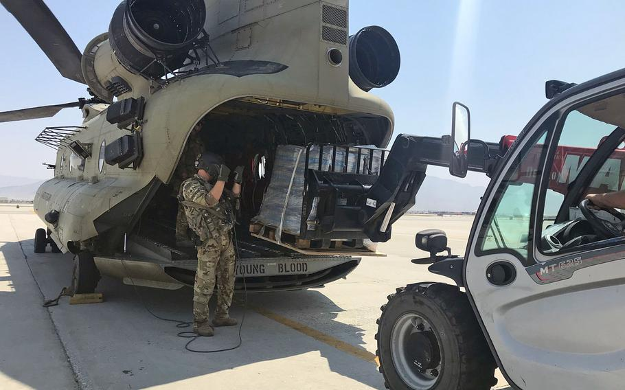 A U.S. Army C-47 Chinook helicopter is loaded with pallets of supplies, as the U.S.-led NATO mission in Afghanistan teamed up with local forces to deliver supplies to civilians affected by recent floods.