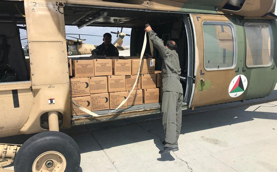An Afghan helicopter is loaded with boxes of Meals, Ready to Eat. The U.S.-led NATO mission in Afghanistan teamed up with local forces to deliver supplies to civilians affected by recent floods.