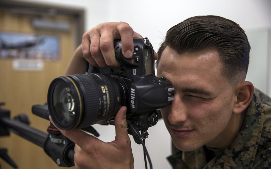U.S. Marine Corps Lance Cpl. John Hall, a combat photographer, takes a picture in the promotion photo studio at  Marine Corps Air Station in Yuma, Ariz., in June 2019. In a move to fight racial and gender bias, photos will no longer be used by promotion boards or in the selection process for opportunities such as training and assignments, the Marine Corps has said.