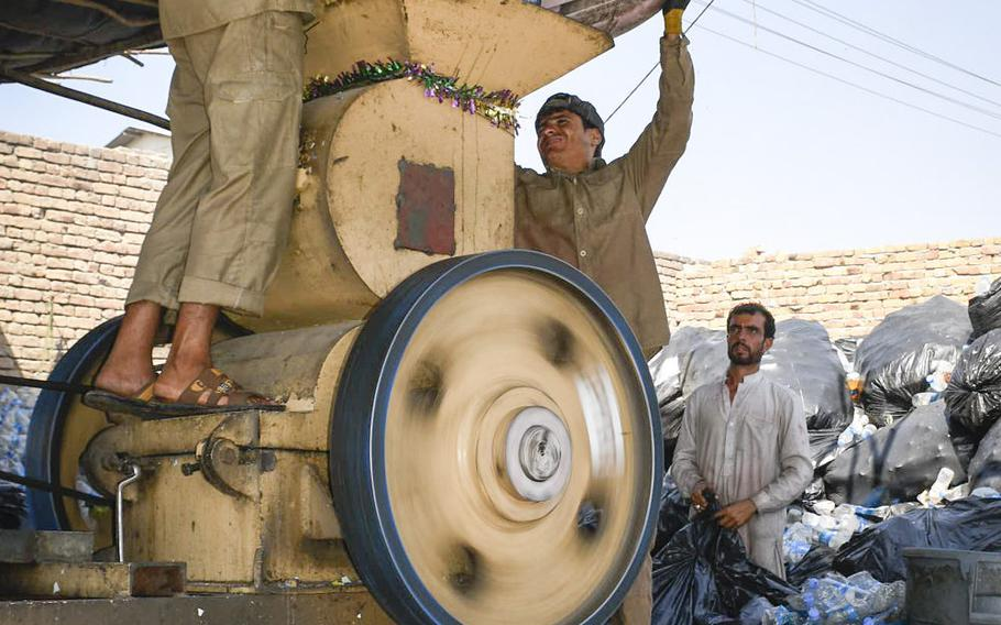 Workers shred plastic bottles from the U.S. Embassy on Aug. 17, 2020 at a recycling site near Kabul airport that the Afghan government says is illegal.