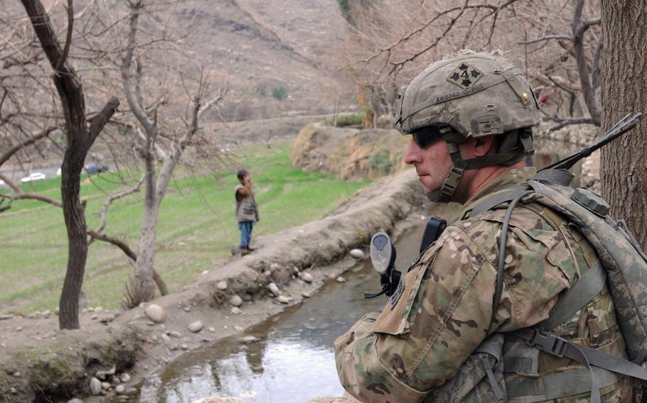 U.S. Army Sgt. Michael Kreuger, Jr., pulls security during a meeting with village elders in the Wata Poor District, Afghanistan, in 2010. Kreuger's son Trenton deployed to Afghanistan in 2018.